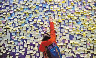 一名孩子将自己的心愿卡贴在重庆科技馆的心愿墙上.孩子们有的希...