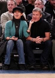 鸭舌帽,身旁的白人男子一头银灰发,明显比她年长很多.两人坐在不...