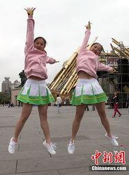 ...图为双胞胎姐妹在广场上跳跃,宣扬自己的青春和激情.    摄 -五四...