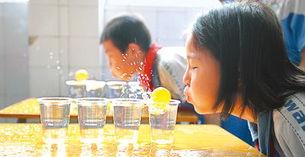 广州海珠区外来工子女学校万翔学校,孩子们在玩吹乒乓球游戏.-外...