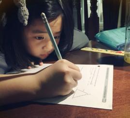着蝴蝶结发卡,趴在桌上写作业.此外,她还嘟嘴瞪眼,将铅笔放在嘟...