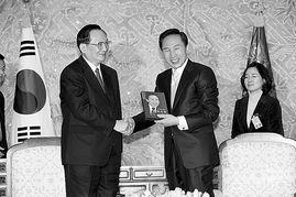 ...唐家璇(左)向韩国新任总统李明博(中)赠送从中国带来的特殊礼...