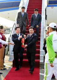 ...前左)和广州市市长万庆良(前右)共同手持火种灯走下飞机舷梯....
