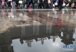...6日 身影已在归乡路 这是2月5日在北京站广场拍摄的旅客和建筑物的...