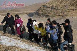 治沙英雄王有德(左)向媒体记者们作着介绍:麦草方格就是这样治沙...