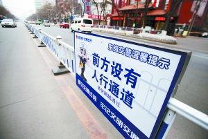 道路隔离栏上装的卡通提示牌.本报记者 -东岗交警安装卡通提示牌 勿...